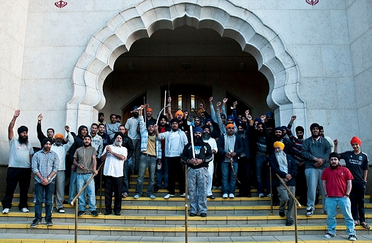 A group of Sikhs standing guard outside Southall Gurdwara Sahib